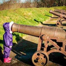 Девочка смотрит в ствол пушки